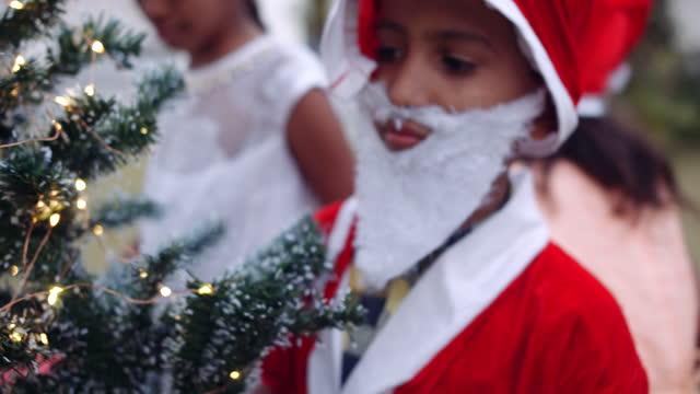 kid dressed as santa looks carefully at a tree decorated with lights - weihnachtsmütze stock-videos und b-roll-filmmaterial