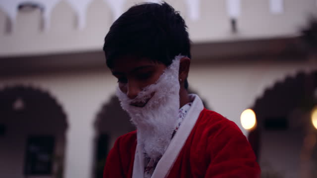 kid dressed as santa taking off his hat as he is tired - weihnachtsmütze stock-videos und b-roll-filmmaterial