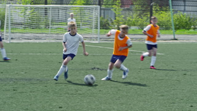 Kid dribbling ball and kicking it during soccer match