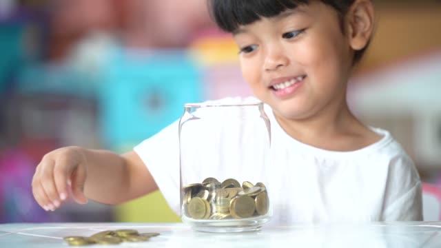 vidéos et rushes de kid dropping coins into the glass for saving the money. selective focu - tirelire
