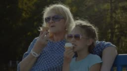 Kid eating eating icecream with grandmother outdoor