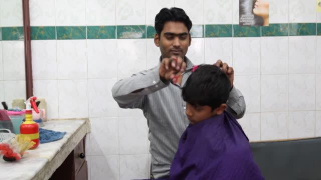 vídeos de stock, filmes e b-roll de kid getting a haircut. - um dia na vida