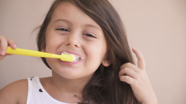 Kid girl brushing teeth