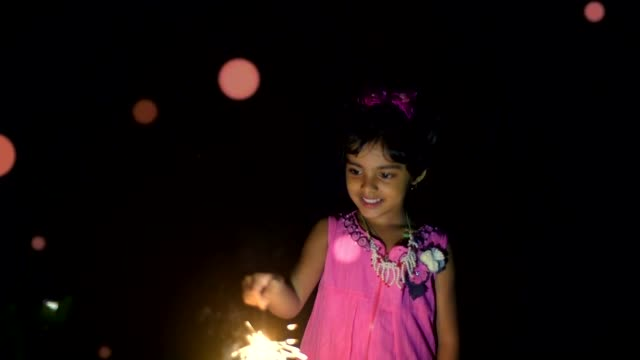 a kid girl celebrating diwali/christmas with sparkler in bokeh background - kolkata stock videos & royalty-free footage