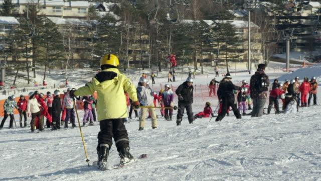 Kid going uphill sideways wearing skis in Pyeongchang (2018 Winter Olympics)