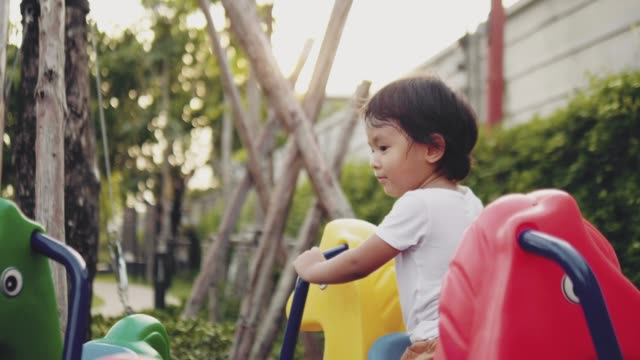 kind hat spaß an merry-go-runde - kinderspielplatz stock-videos und b-roll-filmmaterial