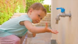 Kid holding empty plastic bottle near tap. Private kindergarten background. Preschooler playing on backyard in the summer. Montessori concept. Playing with water. Tactile exercises on fresh air