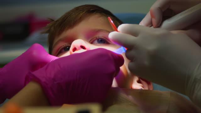 stockvideo's en b-roll-footage met kind in tandheelkundige kantoor - beschermende handschoen