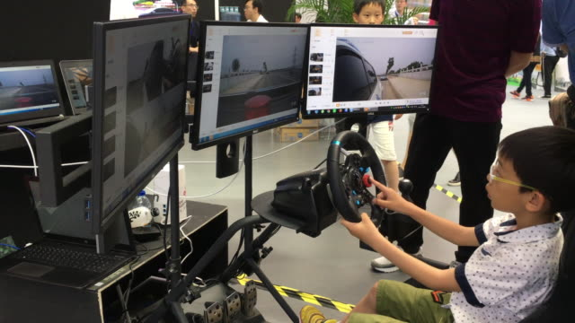 a kid is experiencing remote controlled driving on the 3rd world intelligence congress the 3rd world intelligence congress one of the most important... - remote controlled stock videos and b-roll footage