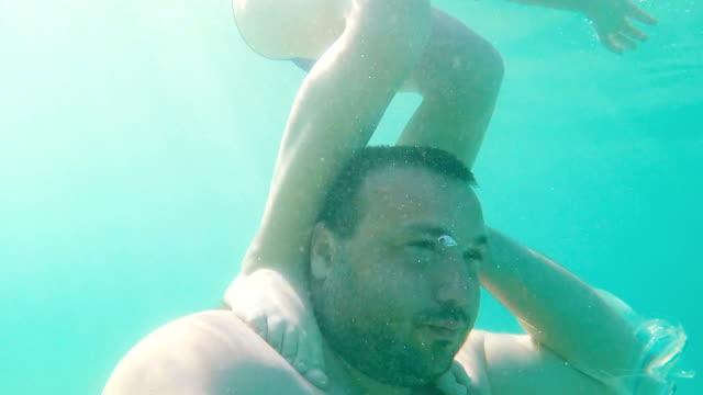 Kid is making faces underwater