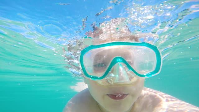 Kind macht Gesichter unter Wasser