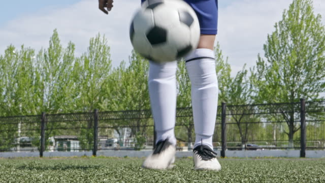 kid juggling soccer ball with feet and then kicking it at camera - juggling stock videos & royalty-free footage