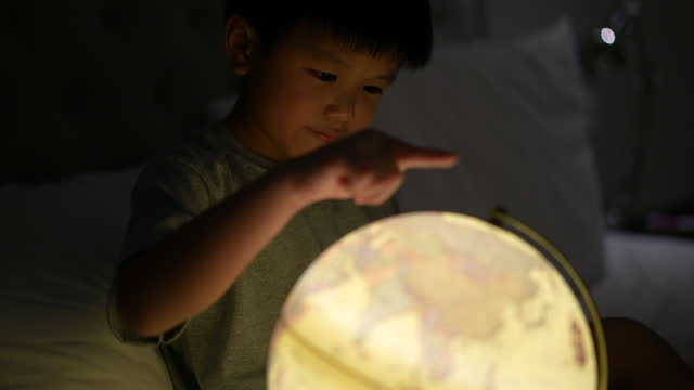 kid learn about the globe with glass magnifier. concept self-learning and environment - childhood stock videos & royalty-free footage