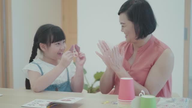 vidéos et rushes de enfant apprenant à créer la peinture de papier et l'artisanat avec sa mère - origami