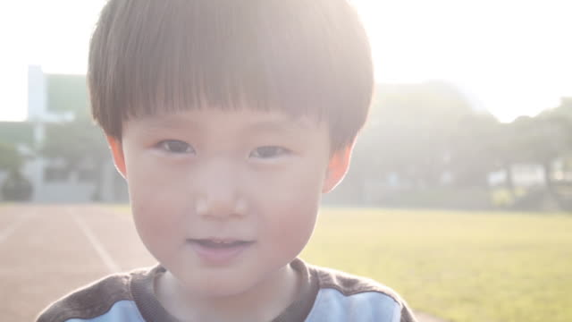 a kid looked camera with smiling face - 男点の映像素材/bロール