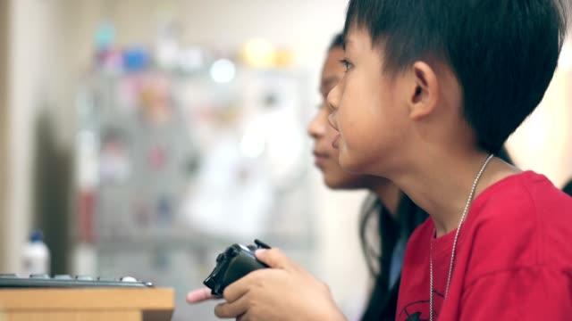 kind spielt videospiel mit fokussierung auf gaming-controller - um geld spielen stock-videos und b-roll-filmmaterial