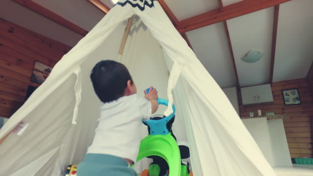 kid pushing toys car in the tent at home. - ワイドショット点の映像素材/bロール