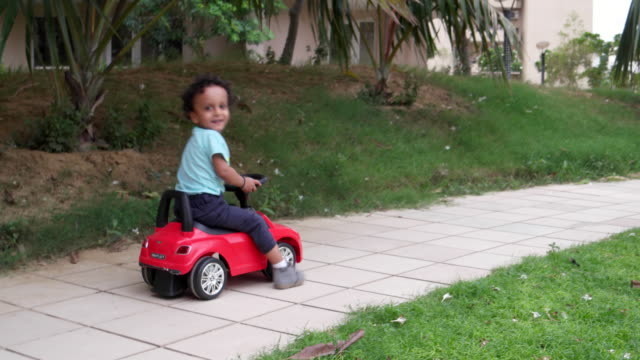 a kid reveres his car and runs away from the camera all excited in a public playground - toy stock videos & royalty-free footage