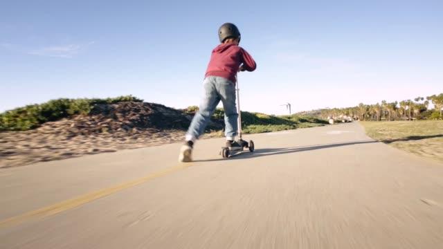 kid riding scooter - santa barbara stock-videos und b-roll-filmmaterial
