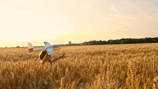 slo mo キッドを走る小麦のフィールドに飛行機トーイ - 少年点の映像素材/bロール