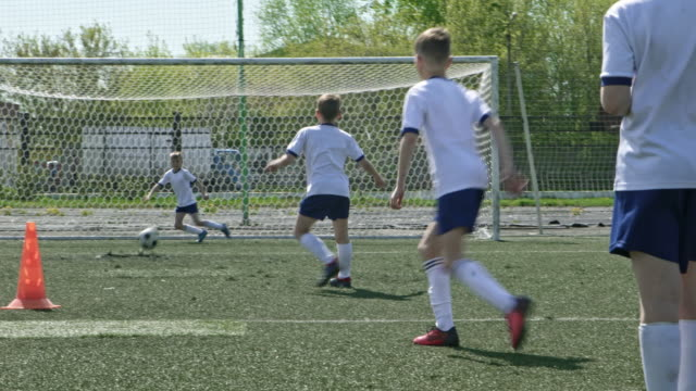 Kid scoring a goal during training on outdoor stadium
