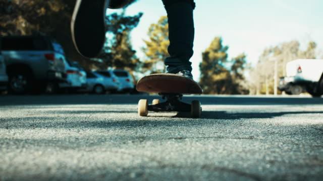vídeos de stock, filmes e b-roll de kid skateboards in parking lot, slow motion - meninos adolescentes