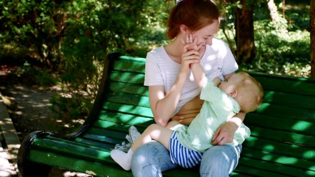 vídeos de stock e filmes b-roll de kid sucking breast and falling asleep - banco de parque