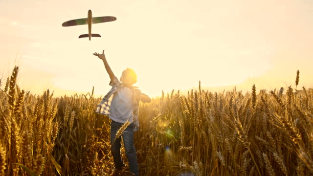 slo mo kid throwing airplane toy in wheat field - boys stock videos & royalty-free footage