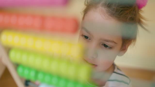 Kid using abacus, slow motion, handheld shot