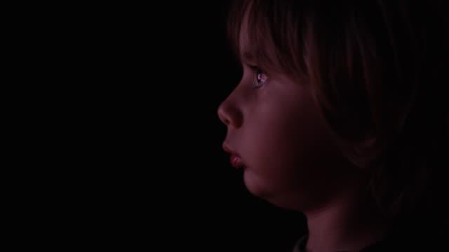 vídeos de stock e filmes b-roll de kid watching television in the dark - staring