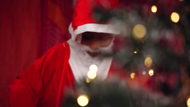 kid wearing santa costume bigger is snapping his hands playfuly - weihnachtsmütze stock-videos und b-roll-filmmaterial
