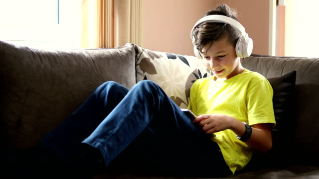 kid with headphones using digital tablet at home - one teenage boy only stock videos & royalty-free footage