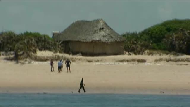 Kidnapped British woman released by Somali pirates T13091112 Lamu Kiwayu Safari Village EXT Detectives on beach of holiday village where Judith...
