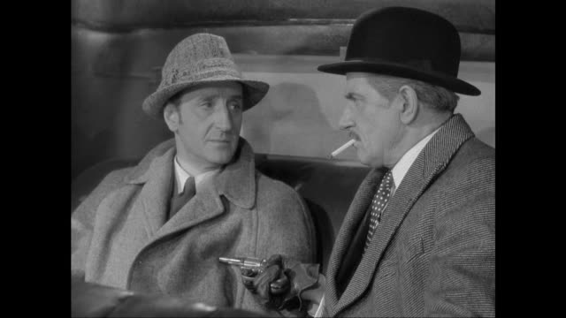 1946 kidnapped sherlock holmes (basil rathbone) steals handcuff key from captor - sherlock holmes stock videos & royalty-free footage