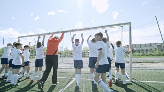 kids and coach placing soccer goals on field - tor konstruktion stock-videos und b-roll-filmmaterial