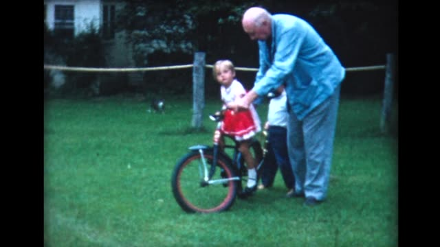 1960 kids and grandparents play with bikes - di archivio video stock e b–roll