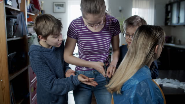 kids are cutting mother's hair during the covid-19 pandemic - effort stock videos & royalty-free footage