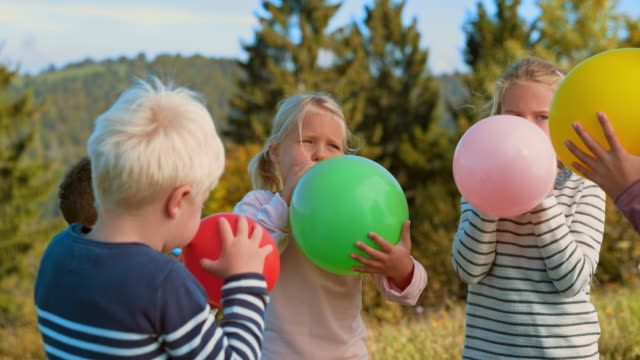 slo mo bambini che soffiano palloncini all'esterno in una giornata di sole - soffiare video stock e b–roll