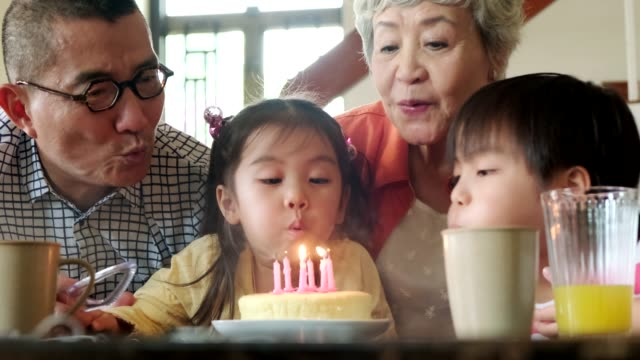 kids blowing out candles on a birthday cake - image stock videos & royalty-free footage