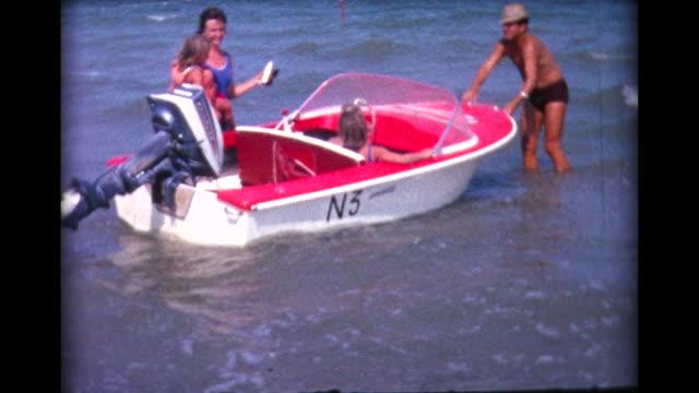 1964 kids board small outboard motor boat - alphabet stock-videos und b-roll-filmmaterial