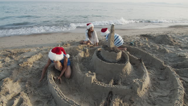 Kids building sandcastle of beach on summer Christmas