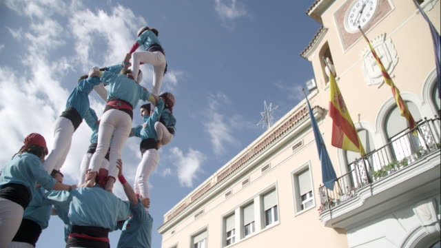 kids climbing to the top of castellers human pyramid - human pyramid stock videos and b-roll footage
