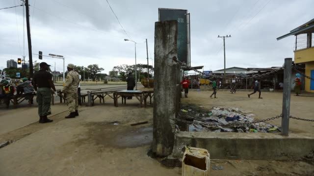 vídeos y material grabado en eventos de stock de kids continue to play while armed police and afl block the entrance to waterside market king zolu duma bridge normally packed lies empty after the... - liberia