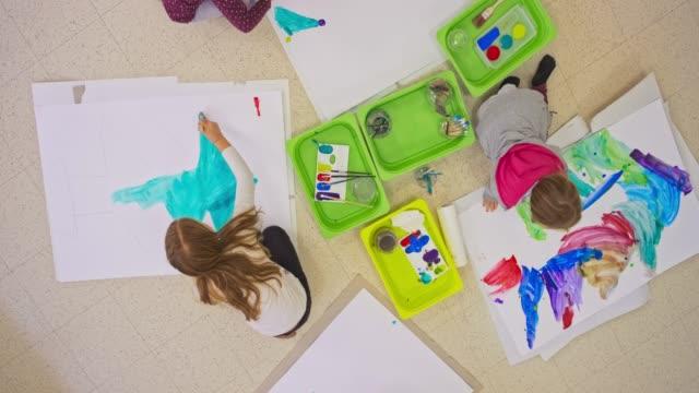 vídeos de stock, filmes e b-roll de miúdos que criam a pintura que senta-se no assoalho na sala de aula - desenhar atividade