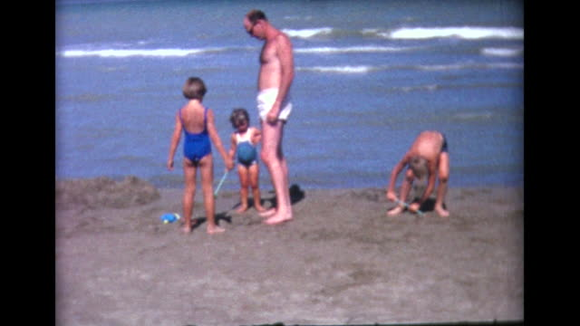 1964 kids digging in sand on lido beach - alfabeto video stock e b–roll