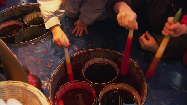 vídeos de stock, filmes e b-roll de ms kids dipping candles in dye at christmas market (kinderweihnacht) / nuremberg, bavaria, germany - tintura