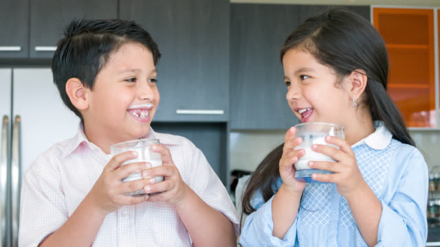 vídeos de stock e filmes b-roll de kids drinking milk at home - leite