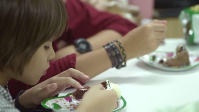vídeos de stock, filmes e b-roll de miúdos que comem o bolo delicioso - comida doce
