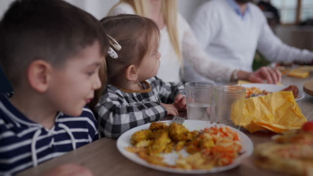 kids eating tasty food during lunch with their parents at friends house - 2 3 anni video stock e b–roll