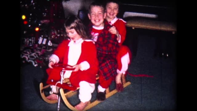 1966 kids enjoy christmas and new sled in living room - christmas tree stock videos & royalty-free footage